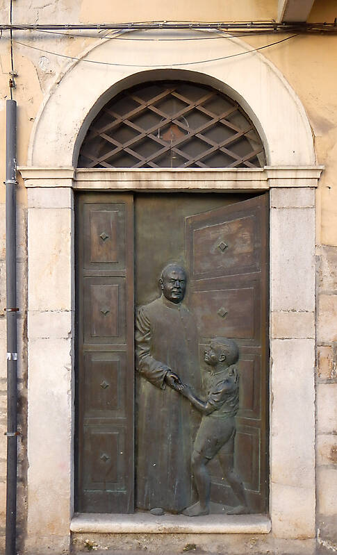 bronze door with prist and kid