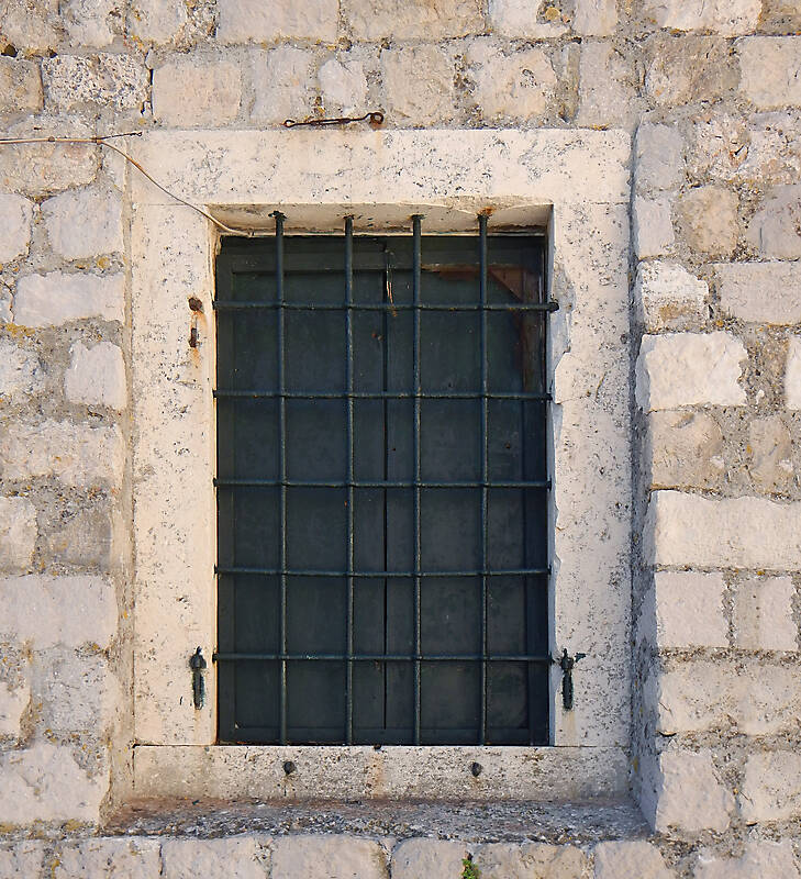old barred window with stone frame 7