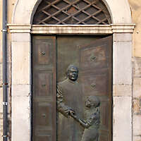 bronze door with priest and kid