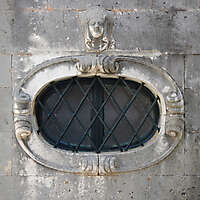 rounded old medieval window with grate 12