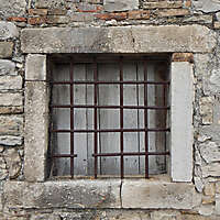 old medieval window stone and rusty cage